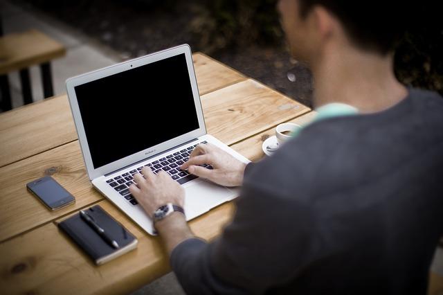Laptopon író férfi